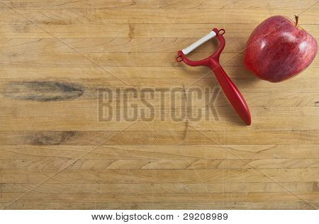 Apple And Peeler On A Cutting Board