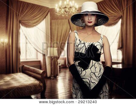 Beautiful woman in hat in luxury room