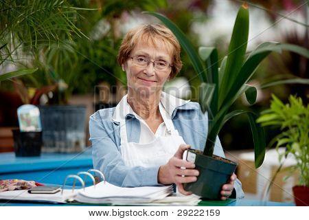 Portret van een senior vrouw die werkt in een tuincentrum