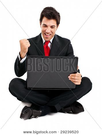 Victorious businessman with arms raised sitting in front of his laptop isolated on white