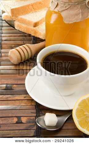 cup of coffee with beans and sweets on wood