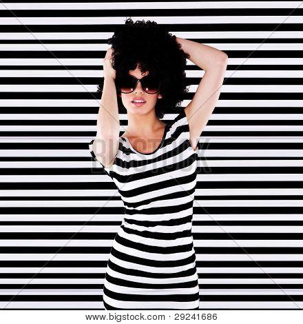 Señora funky en top de rayas con pie de peinado afro frente a rayas blanco y negro fondo
