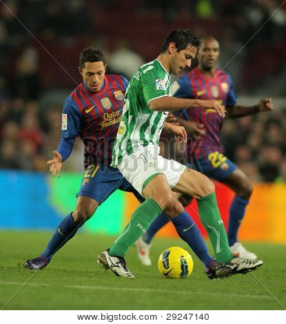 BARCELONA - JAN 15: Roque Santa Cruz(R) of Real Betis vies with Adriano Correia(L) of FC Barcelona during the Spanish league match at the Camp Nou stadium on January 15, 2012 in Barcelona, Spain