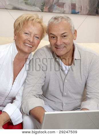 Portrait of a senior couple shopping using computer laptop.