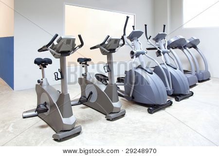 elliptical cross trainer, stationary bicycle and treadmill in gym