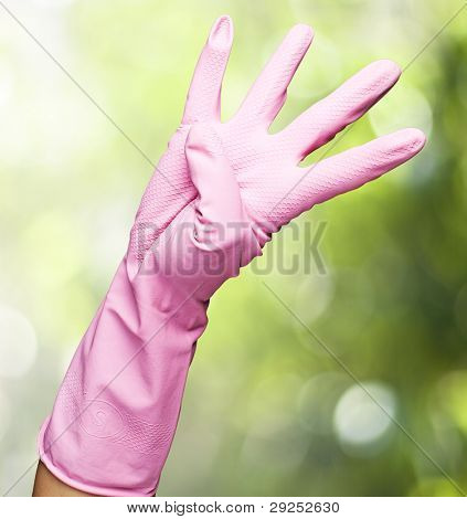 pink glove of gesturing a number four against a nature background