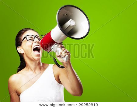 portrait of a middle aged woman shouting using a megaphone over a green background