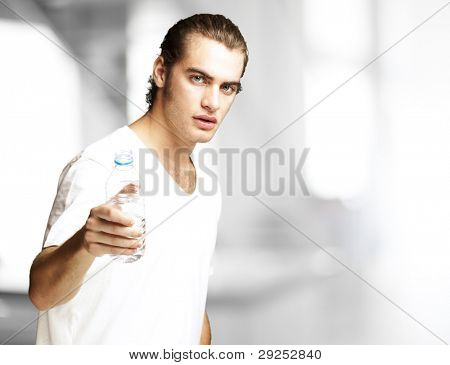 portrait of a handsome young man offering a water bottle indoor