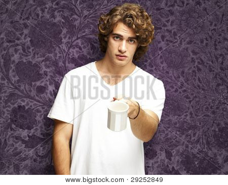 portrait of a young man offering a cup against a vintage purple wall