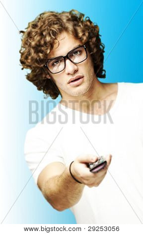 portrait of a young man with glasses changing channel with a remote control over a blue background