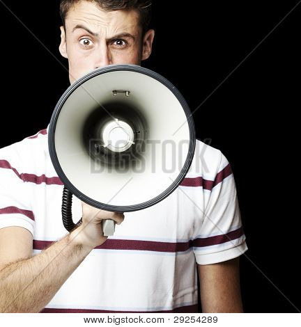 portrait of a young man shouting using a megaphone over a black background
