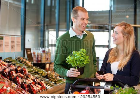 Woman holding mobile phone and looking at man in shopping centre