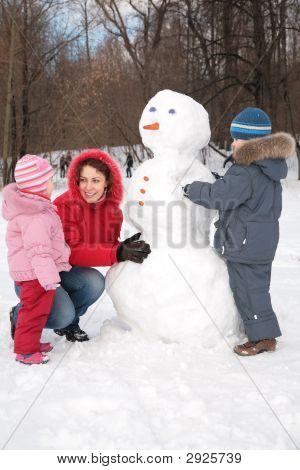 Mother And Children Make Snowman