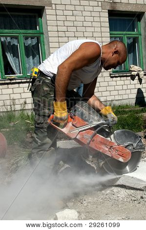 Worker With Industrial Saw Cutting A Concrete Block