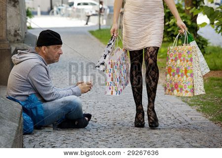 Beggar and a rich young woman with shopping bags