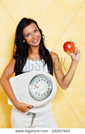 uma jovem mulher com uma balança na mão, sorrindo após uma dieta de sucesso