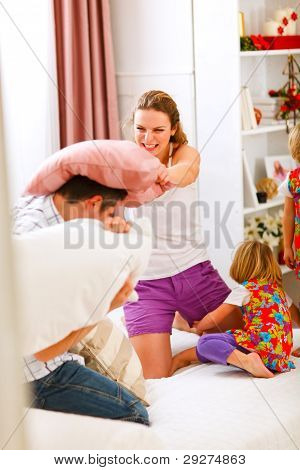 Happy Family Having A Pillow Fight In Bed