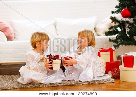 Two Lovely Twins Girl Exchanging Presents Near Under Christmas Tree