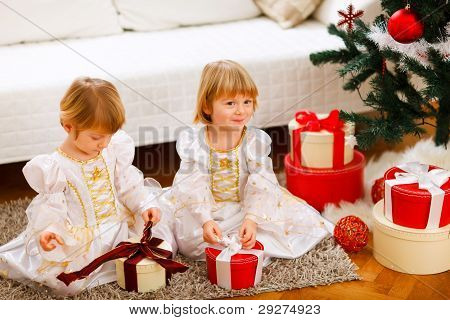 Two Cute Twins Girls Opening Presents Near Christmas Tree