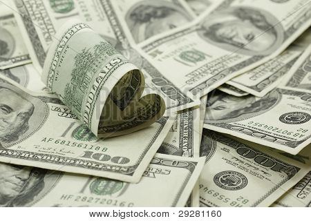 Heart Shaped 100 Dollar Bill On Pile Of Money