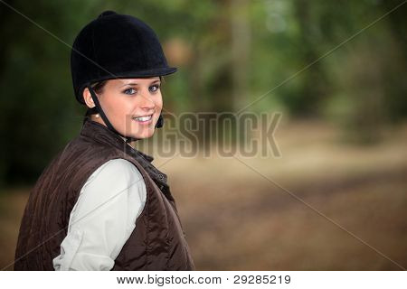 Young female horseback rider on a forest trail
