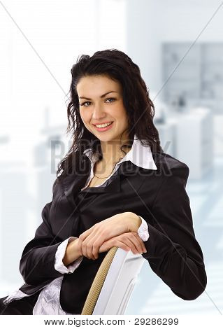 Portrait of young businesswoman sitting in an office chair and smiling