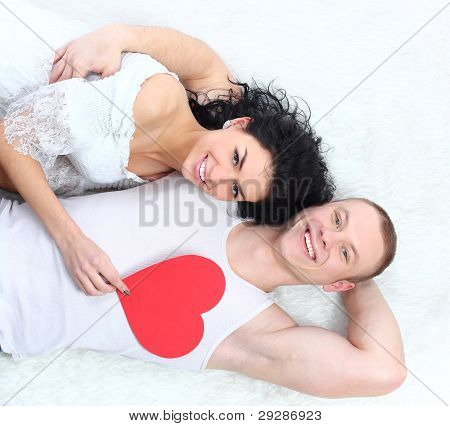 Young lovely couple holding red heart together lyingon the floor happy smile looking at camera valen