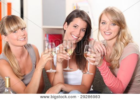 Three female friends drinking wine on sofa