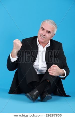 An angry man sitting cross-legged