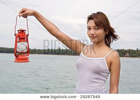mujer que sostiene una lámpara de queroseno