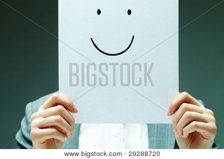 Image of female holding paper with drawn smile by her face