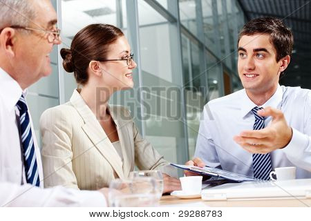 Three business partners sitting in office and interacting at meeting