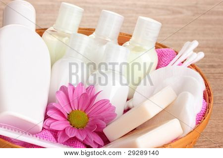 Hotel amenities kit in basket on wooden background