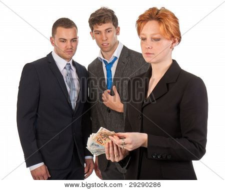 Female Business Woman Is Counting Money With Curious Male Colleagues - Isolated On White