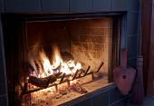 stock photo of cozy hearth  - Fire in a fireplace with bellows and broom - JPG