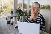 Beautiful Senior Woman Using Laptop At Home. Mature Smiling Woman Looking At Camera While Working Wi poster