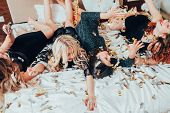 Theme Party. Chill Out. Group Of Girls In Black Relaxing On Bed Under Confetti Rain. Bff Female Gath poster