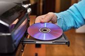 Hand Holding Dvd Inserting To Video Player poster