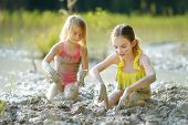 Two Young Sisters Taking Healing Mud Baths On Lake Gela Near Vilnius, Lithuania. Children Having Fun poster