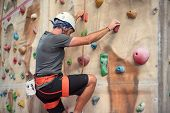 Young Man Practicing Rock Climbing On Artificial Wall Indoors. poster