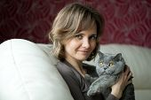pic of fondling  - Pretty young woman playing with a gray cat British breed - JPG