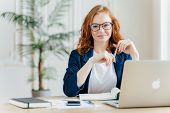 Positive Red Haired Young Female Entrepreneur Watches Business Webinar, Writes Email, Makes Notes In poster