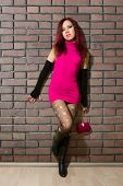 picture of hooker  - girl dressed like hooker posing near brick wall - JPG