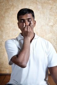 stock photo of pranayama  - Handsome Indian man in white shirt doing nadi suddhi pranayama with Vishnu mudra gesture close - JPG