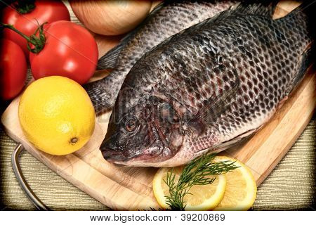 Two Raw Tilapia Fish in Vintage Style Photograph on Cutting Board