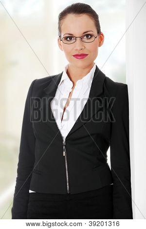 Retrato de exitosa mujer de negocios feliz situación próxima a pared