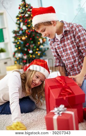 Portrait of happy siblings looking inside big red giftbox on Christmas evening