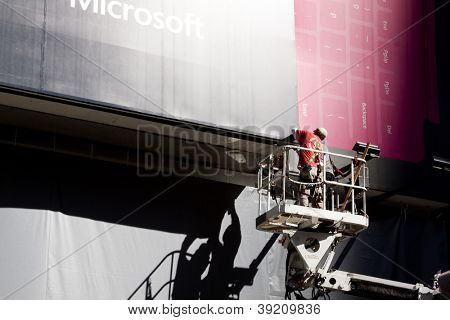 NEW YORK - OCT 18: Two workers on a motorized lift install an advertising billboard for Microsoft in Times Square in New York City on October 18, 2012.