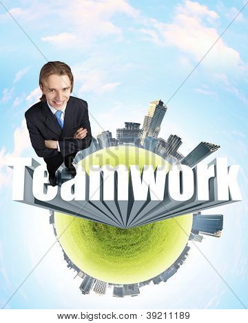Young businessman in suit standing on the word Teamwork