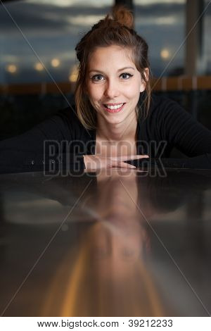 Beautiful woman looking with big smile with slight reflection on table